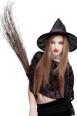 Showy young woman in witch costume with a broom
