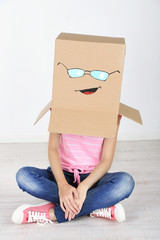 Woman with cardboard box on her head with happy face near wall