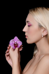 The beautiful young woman with flowers of orchid