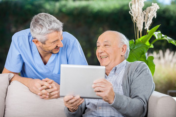 Male Caretaker And Senior Man Laughing While Using Tablet Comput