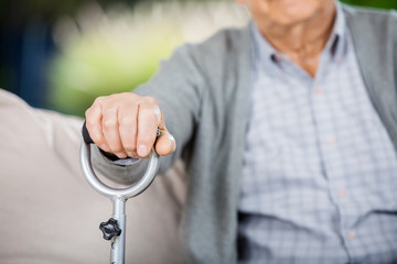 Midsection Of Senior Man Holding Metal Walking Stick