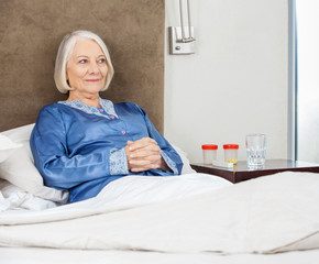 Smiling Senior Woman Relaxing On Bed At Nursing Home
