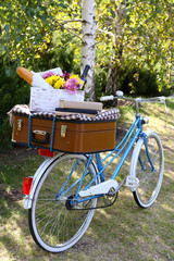 Bicycle and brown suitcase with picnic set