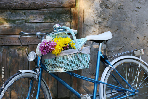 Old bicycle with flowers in metal basket © Africa Studio