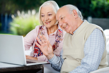 Elderly Couple Video Chatting On Laptop
