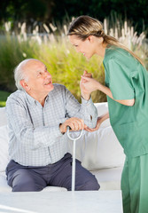 Female Nurse Helping Senior Man To Get Up From Couch