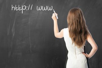 Woman writing URL on blackboard.