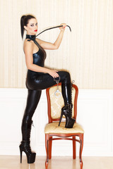 Woman in latex catsuit with whip and handcuffs