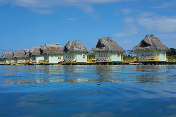 Caribbean over water bungalows with thatched roof