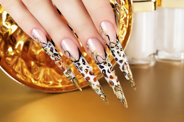 Hand with beautiful nails on gold background.