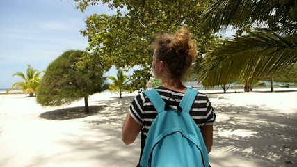Traveller Girl with Backpack is Reading a Map on Beach.