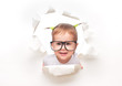 child baby girl in glasses peeping through a hole in white paper