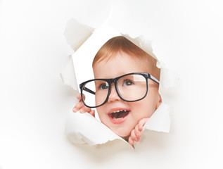 Funny  child with glasses peeping through hole in white  paper