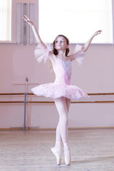 Ballet studio. Petite ballerina posing at camera