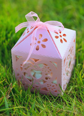 Pink carved gift box on green grass