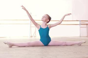 Flexible little ballerina posing sitting on split
