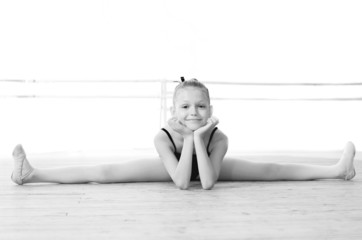 Black and white photo. Cute ballerina doing split