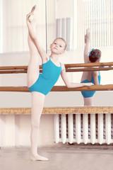 Flexible young ballerina doing vertical split