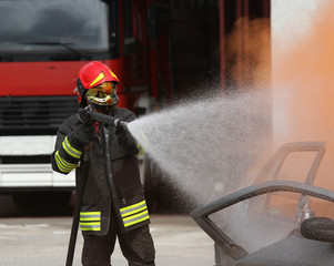 firefighter with helmet off the car burned with the foam