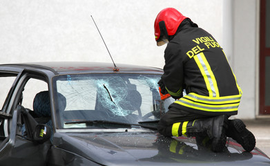 Italian firemen break the windshield of the car to release the i