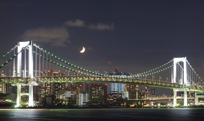 Tokyo rainbow bridge and moon at night time