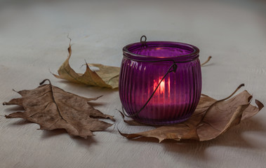 Glass candle holder with burning candle