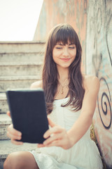 beautiful young woman with white dress using tablet