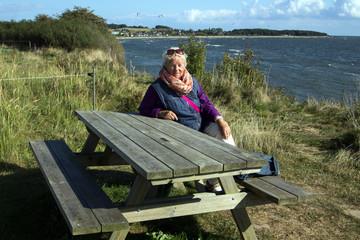 Seniorin im Urlaub sitzt auf einer Holzbank