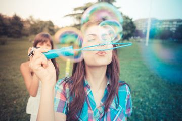 beautiful hipster young women sisters friends blowing bubbles