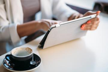 Businesswomen using tablet computer in cafe on coffee break