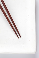 Wood brown chopstick on ceramic white plate