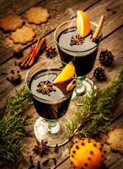 Mulled wine with orange slices on wood - winter warming drink