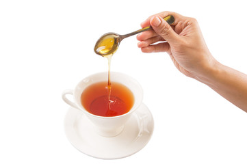 Female hand mixing honey with tea over white background