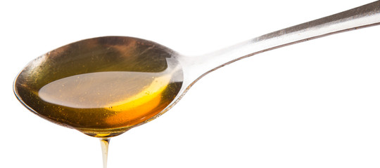A spoon of honey over white background