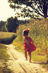 cute Little girl in run in a summer field