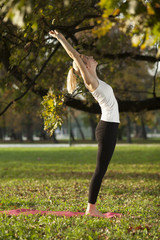 woman practicing yoga in a park