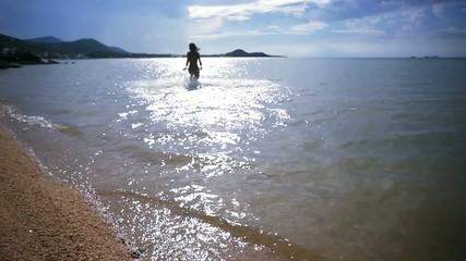 sexy woman in bikini running into  sea to meet the sun on Koh
