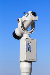 White paid tourist telescope on blue sky background