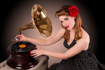 Beautiful young pin-up listens to retro gramophone