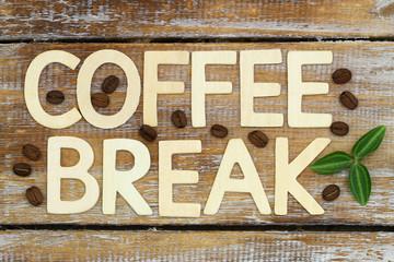 Coffee break written with wooden letters on rustic wood