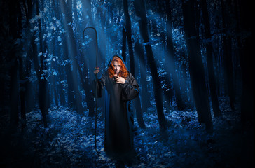 Witch with staff in night forest