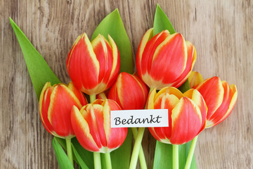 Red and yellow tulips with word 'bedankt' (thank you in Dutch)