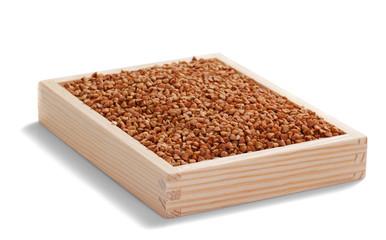buckwheat grains in wooden box on white