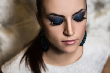 Portrait of a woman with blue smokey eyes make-up and bijou