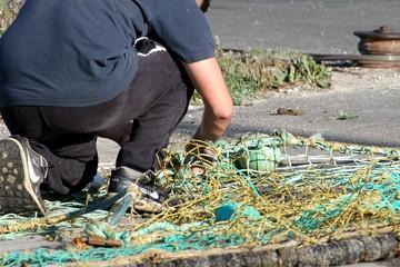marin pêcheur réparant un filet de pêche sur un quai