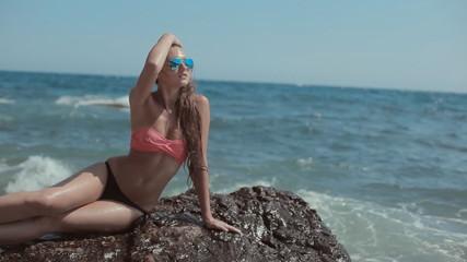Beautiful  sexy model in bikini sitting on a rock near the sea