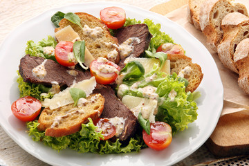 Salad with slices of roast beef with truffle sauce and toasts