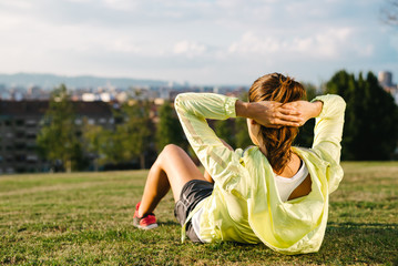 Woman doing situps and exercising in city park
