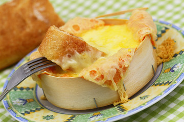 French bread dipped into baked cheese, close up