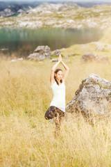 Junge Frau macht Yogaübungen im hohen Gras